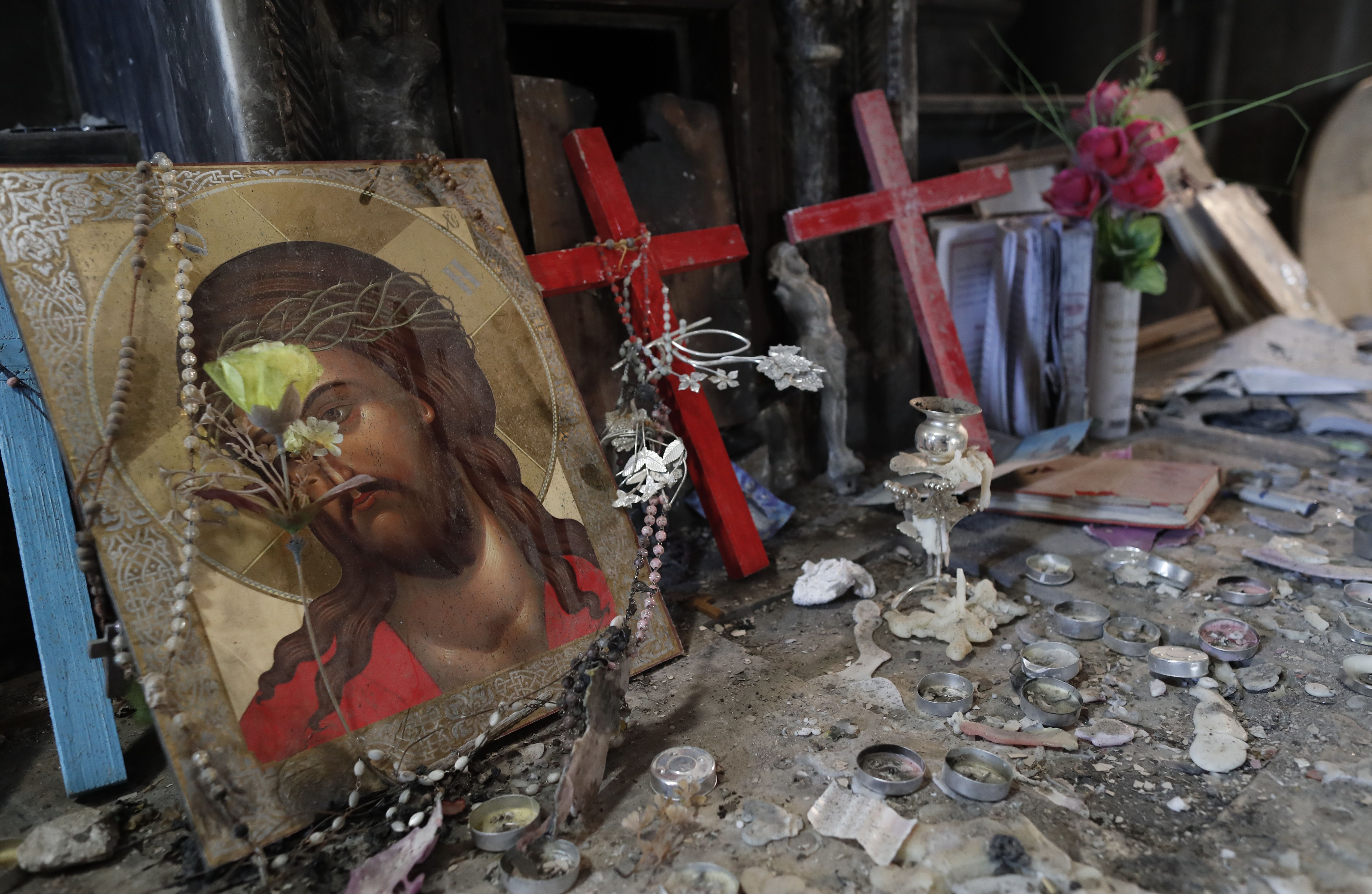 A portrait of Jesus Christ is seen inside the heavily damaged Church of the Immaculate Conception in the Christian town of Qaraqosh, also know as Hamdaniya, some 30 kms east of Mosul, on December 4, 2016, one month after Iraqi forces recaptured it from Islamic State (IS) group jihadists. / AFP / THOMAS COEX (Photo credit should read THOMAS COEX/AFP/Getty Images)
